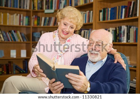 Senior couple enjoying a good book together in the library. - stock photo