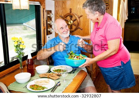 Senior couple enjoying a healthy meal in their luxury motor home. - stock photo