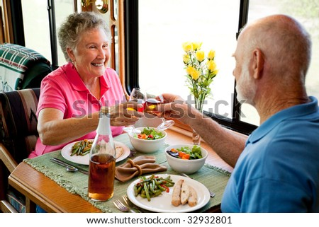 Senior couple enjoying a romantic dinner in their motor home. - stock photo