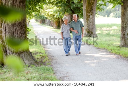Senior couple enjoying a walk in the park - stock photo