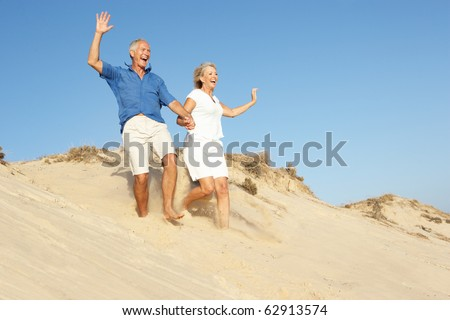 Senior Couple Enjoying Beach Holiday Running Down Dune - stock photo