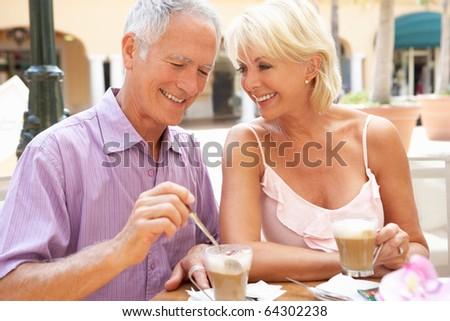 Senior Couple Enjoying Coffee And Cake In Cafe - stock photo