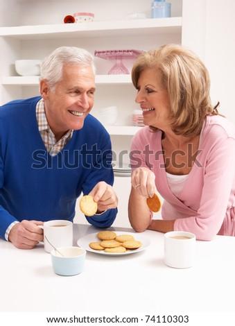 Senior Couple Enjoying Hot Drink In Kitchen - stock photo