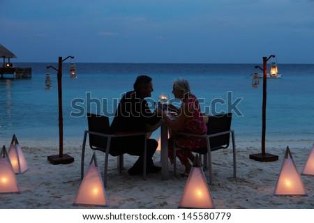 Senior Couple Enjoying Late Meal In Outdoor Restaurant - stock photo