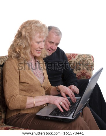 Senior couple enjoying looking at images of their family on a laptop computer - stock photo
