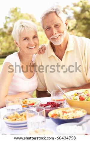 Senior Couple Enjoying Meal In Garden - stock photo