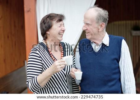 Senior Couple Enjoying Snack At Outdoor Cafe  - stock photo