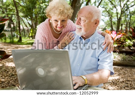 Senior couple enjoying the computer outdoors in a natural setting. - stock photo