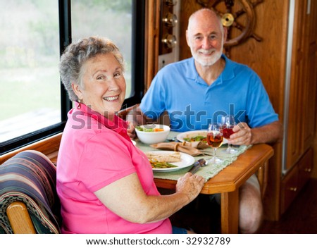 Senior couple enjoys a healthy lunch in the kitchen of their motor home. Focus on the wife. - stock photo