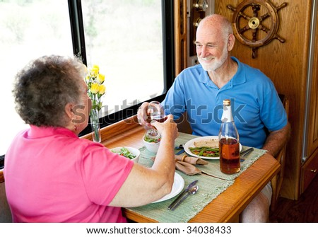 Senior couple enjoys a romantic meal in the kitchen of their motor home. - stock photo