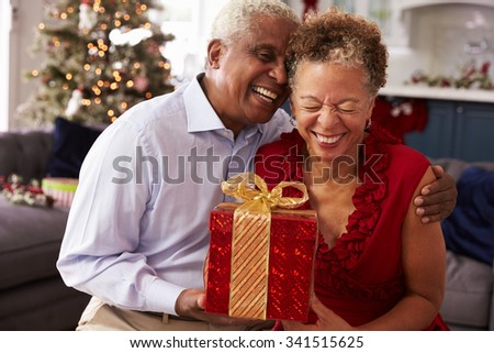 Senior Couple Exchanging Christmas Gifts At Home - stock photo