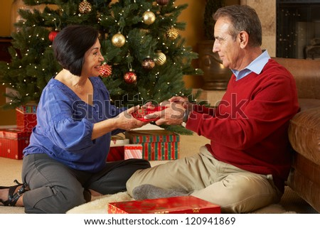 Senior Couple Exchanging Gifts In Front Of Christmas Tree