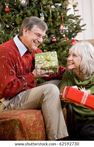 Senior couple exchanging presents by Christmas tree