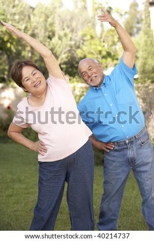 Senior Couple Exercising In Garden - stock photo