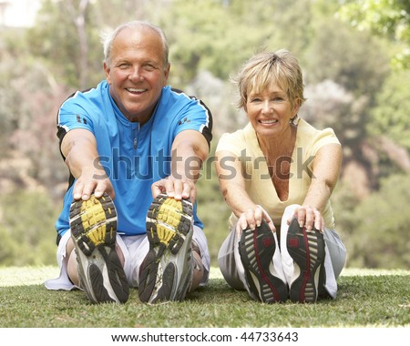 Senior Couple Exercising In Park - stock photo