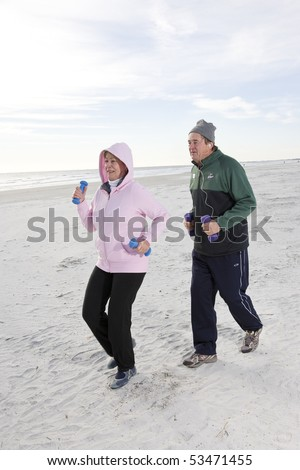 Senior couple exercising, jogging on beach with hand weights - stock photo