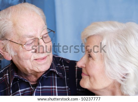 Senior couple , face to face, on blue background - stock photo