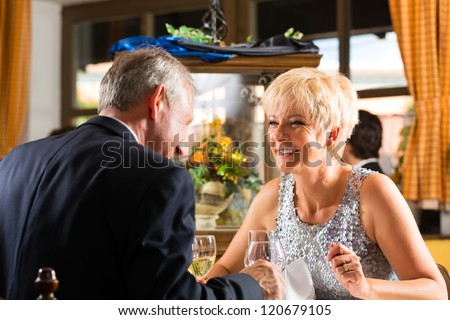 Senior couple fine dining food at table in hotel or elegant restaurant - stock photo