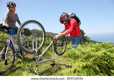 Senior couple fixing broken bicycle chain