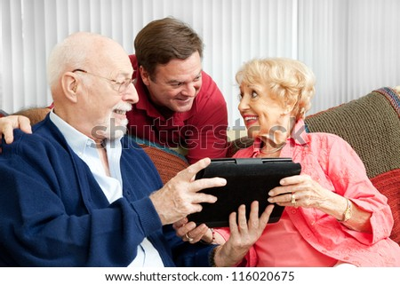 Senior couple get a gift of a tablet PC from their adult son. - stock photo