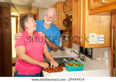 Senior couple get romantic while preparing lunch in their RV. - stock photo