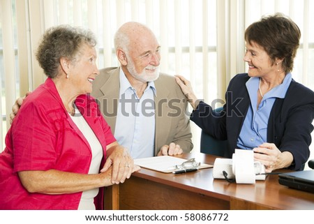 Senior couple gets good news from their accounant. - stock photo