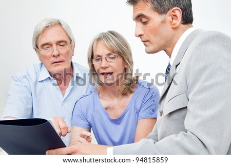Senior couple getting financial advice from consultant at home - stock photo