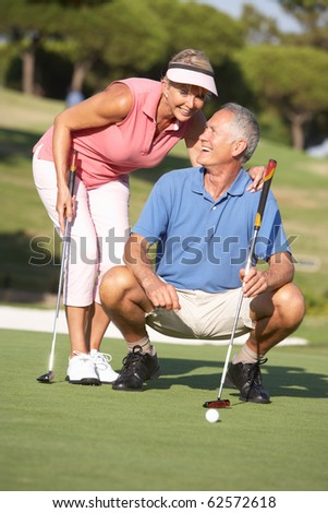 Senior Couple Golfing On Golf Course Lining Up Putt On Green - stock photo