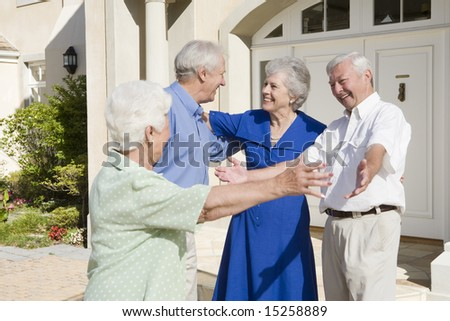 Senior couple greeting friends outside house