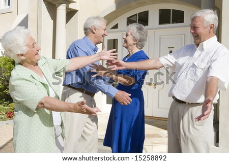 Senior couple greeting friends outside house - stock photo