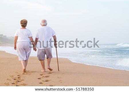 senior couple hand in hand walking on beach - stock photo
