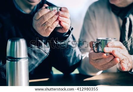 Senior couple hands holding cups with hot coffee - stock photo