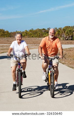 Senior couple has fun riding their bicycles on a tropical vacation. - stock photo