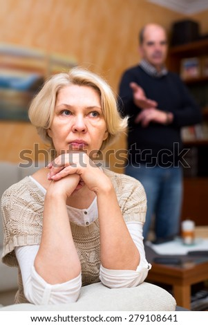 Senior couple having a conflict at home. Old woman sits turned away from her husband who is trying to explain her something