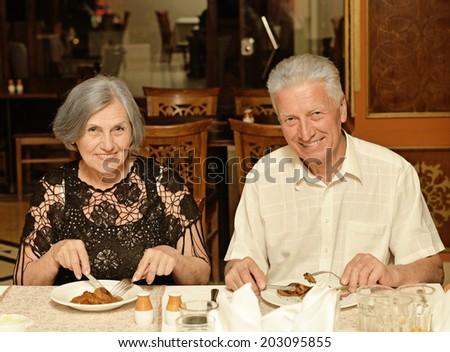 Senior couple having a dinner at restaurant - stock photo