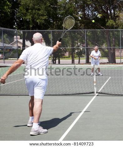 Senior couple having a game on the tennis court. - stock photo