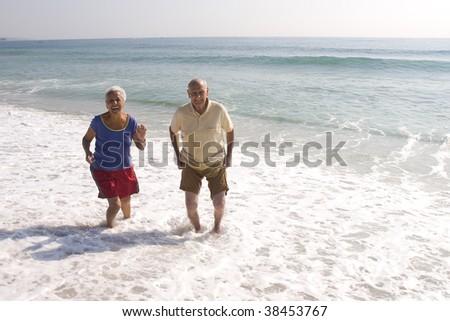Senior couple having a good time at the beach - stock photo