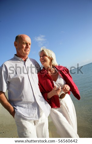 Senior couple having a walk at the seaside - stock photo