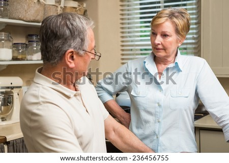Senior couple having an argument at home in the kitchen - stock photo