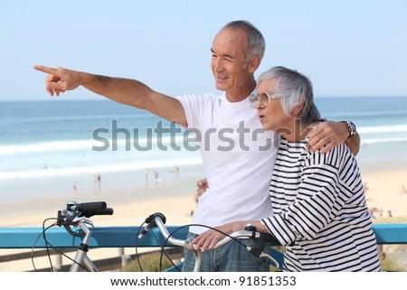 Senior couple having bike ride at the beach - stock photo