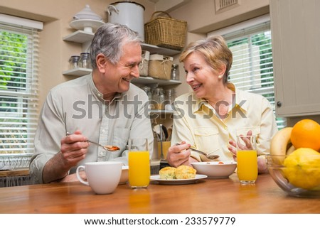 Senior couple having breakfast together at home in the kitchen - stock photo