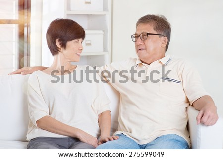 Senior couple having conversation, sitting on sofa at home. Living lifestyle of Asian family. - stock photo