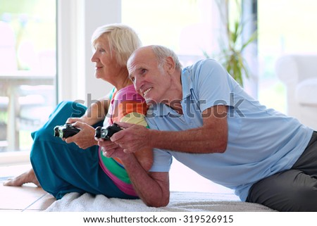 Senior couple having fun at home playing video game holding joysticks in hands lying cozy on the floor in bright sunny living room with big windows. Happy retirement concept.