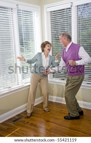 Senior couple having fun dancing in living room - stock photo