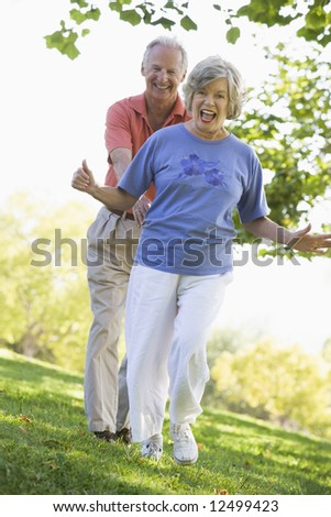 Senior couple having fun in park running on grass - stock photo