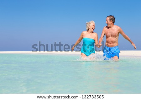 Senior Couple Having Fun In Sea On Beach Holiday - stock photo