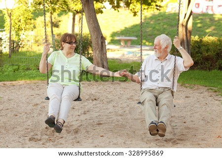 Senior couple having fun on park swings - stock photo