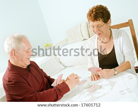 senior couple having fun playing cards at home - stock photo