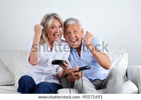 Senior couple having great time playing video game together - stock photo