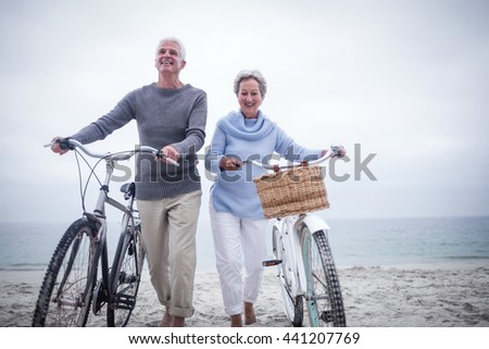Senior couple having ride with their bike on the beach - stock photo
